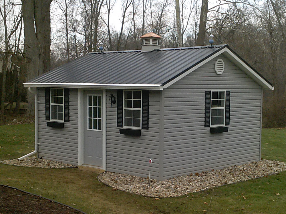 Atlantic style mini barn. Metal roof, vinyl siding, windows. Custom storage building
